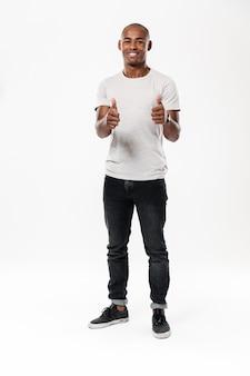 Жизнерадостный молодой африканский человек показывая большие пальцы руки вверх.