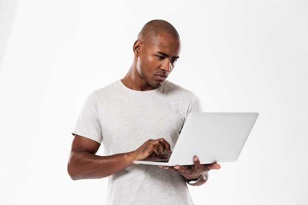 Красивый молодой африканский человек используя портативный компьютер