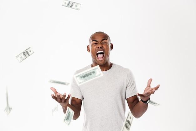 Эмоциональный кричащий молодой африканский человек с деньгами.