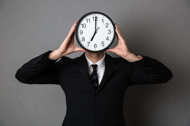 彼の顔の前で時計を保持している黒のスーツを着た若い男