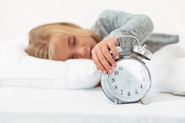 眠そうな少女のクローズアップは彼女の寝室で目覚まし時計をオフに