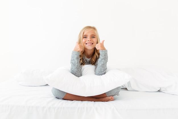 Фотография крупного плана счастливой маленькой девочки сидя с белой подушкой в кровати, показывая большие пальцы руки вверх показывать двумя руками,