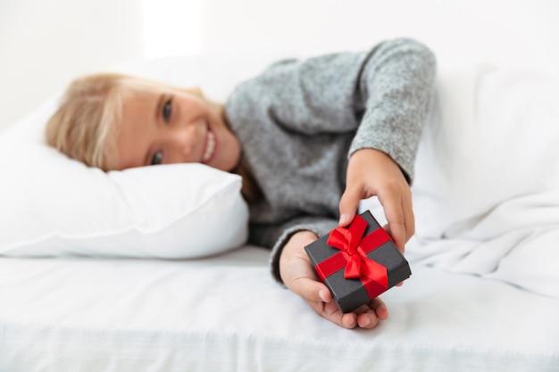 Счастливая маленькая девочка держа малую подарочную коробку пока лежащ в кровати, селективном фокусе