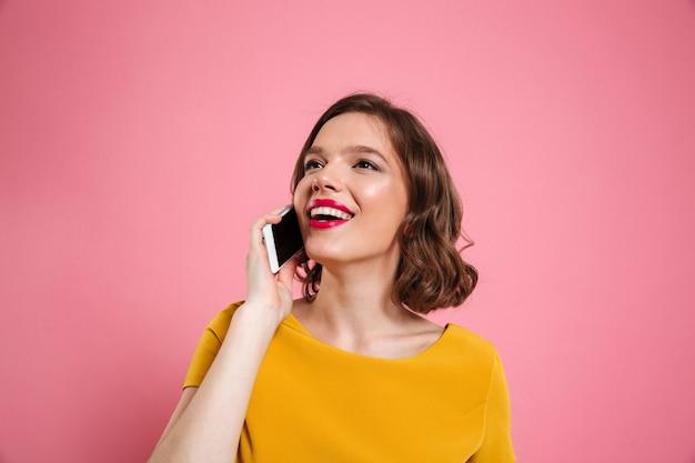 携帯電話で話している笑顔のきれいな女性の肖像画