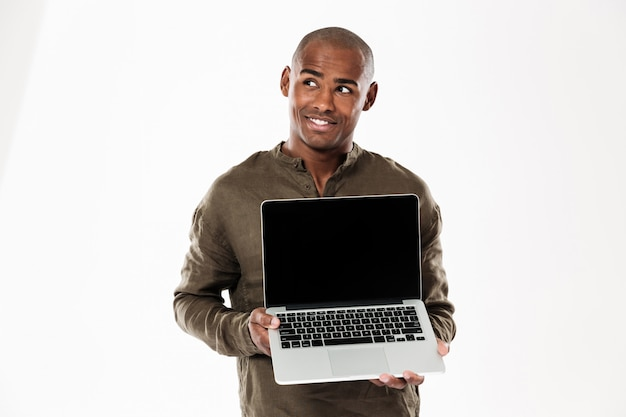 空白のラップトップコンピューターの画面を表示して見上げる物思いにふけるアフリカ人を笑顔