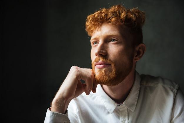 Крупным планом портрет задумчивый рыжий молодой человек