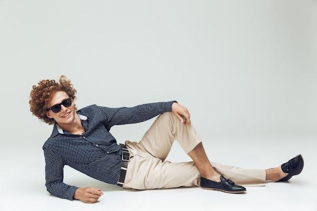 Ретро мужчина в рубашке лежит на полу и позирует