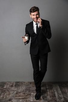 電話で話しているコーヒーを飲む陽気な興奮している若いビジネスマン