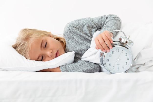 目覚まし時計を保持している眠っている子供のクローズアップの肖像画