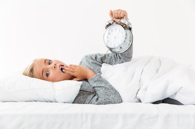 Изумленная маленькая белокурая девушка держит будильник, прикрывая рот лежа на мягкой кровати