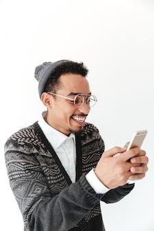 Счастливый молодой африканский человек в чате по телефону.