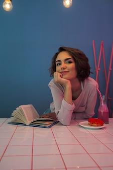 Счастливая молодая девушка сидит за столом с книгой