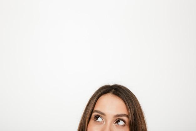 Половина лица загадочной брюнетки смотрит на серый