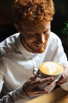コーヒーカップを保持しているハンサムな若い赤毛の男のクローズアップの肖像画