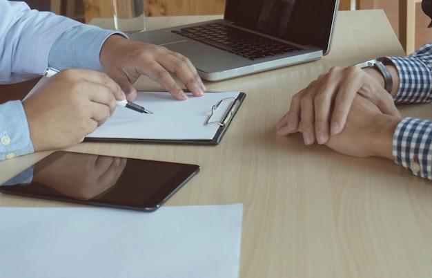 患者と医者のノートを取るか、または白い均一なガウンコートの面接ใでプロの医師を閉じます