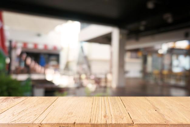 カフェやコーヒーショップのインテリアの抽象的なぼやけた背景の前に空の暗い木製のテーブル。あなたの製品の表示やモンタージュに使用することができます。