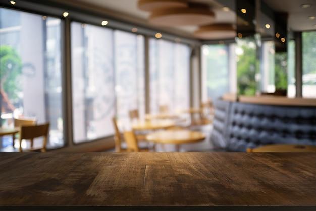 コーヒーショップの抽象的なぼやけた背景の前に空の暗い木製のテーブル。あなたの製品を表示またはモンタージュするために使用することができます。製品の表示のためにモックアップ