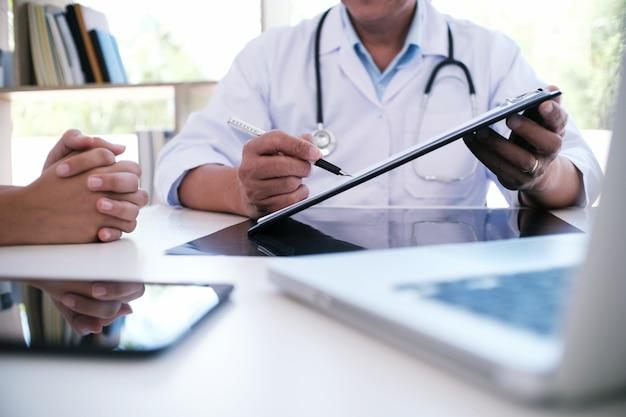 白い均一なガウンコートのインタビューのコンサルティング患者の専門医師