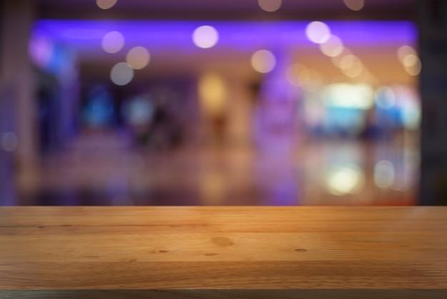 レストランの抽象的なぼんやりしたボーケの背景の前に空の暗い木製のテーブル。あなたの製品を表示またはモンタージュするために使用することができます。