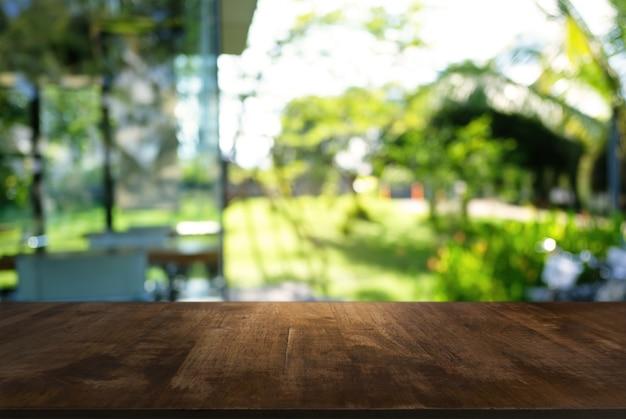 コーヒーショップの抽象的なぼやけた背景の前に空の木製のテーブル