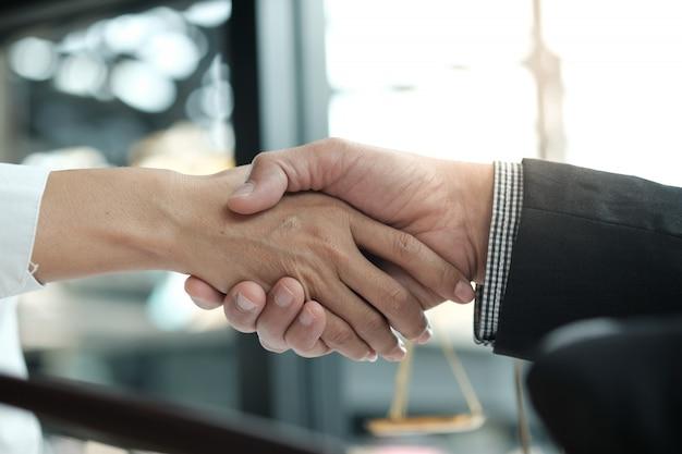 クライアントとの弁護士ハンドシェイク。ビジネスパートナーシップ会議成功のコンセプト。
