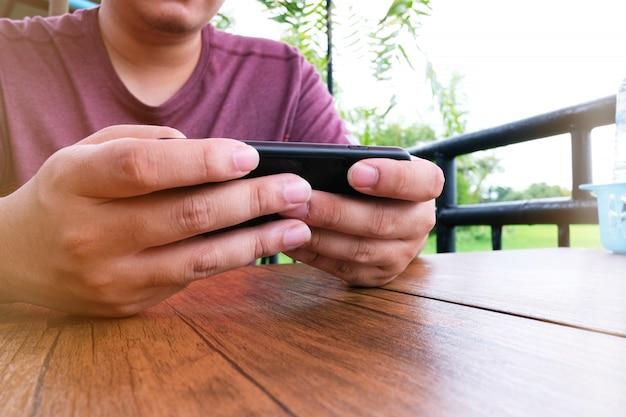 男は携帯電話でゲームをプレイします。