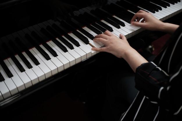 美しいアジアの女の子はピアノを弾くことを学ぶ。
