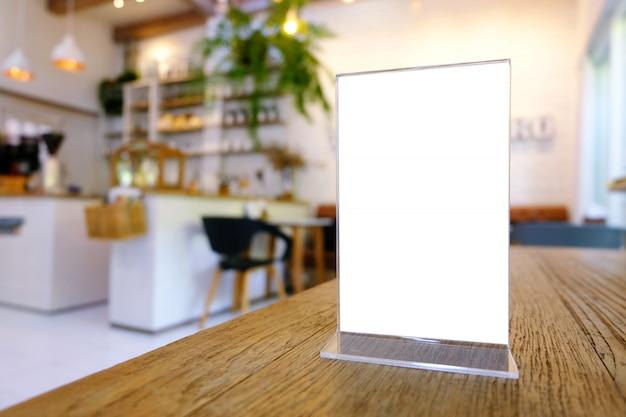 バーレストランカフェの木のテーブルの上に立っているメニューフレームをモックアップします。テキスト用のスペース