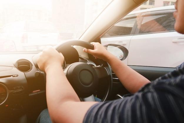 Укомплектуйте личным составом управлять с обеими руками на фокусе рулевого колеса селективном. концепция безопасного вождения.
