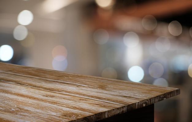 レストランの抽象的なボケ背景の前に空の暗い木製のテーブル