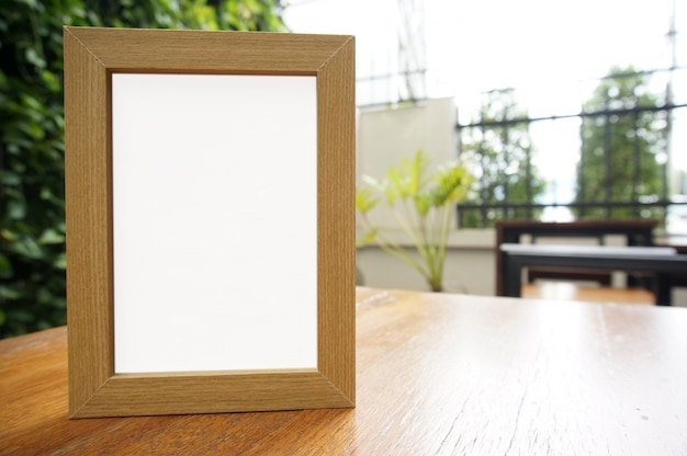 モックアップバーレストランカフェの木製テーブルにブランクの白いフレームが立っています。テキストのスペース。製品表示モンタージュ。