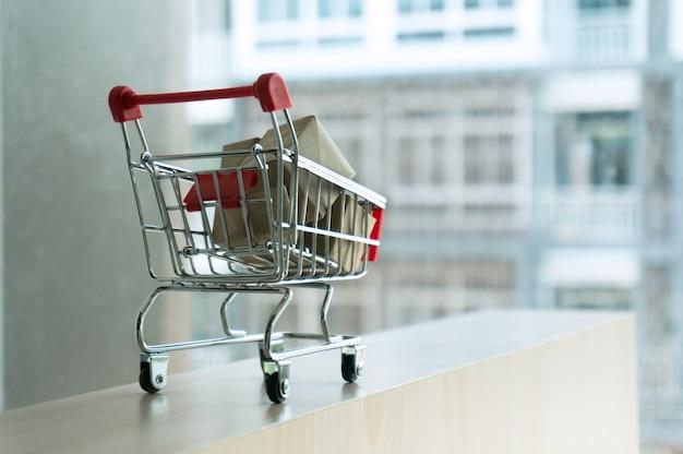 Корзина с картонной коробкой бумажные коробки. тележка с подарками концепция шоппинга. селективный фокус