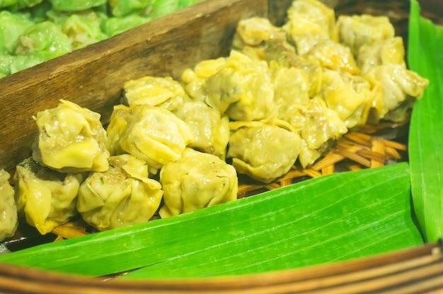 中国の蒸し餃子、竹の蒸し蒸し蒸し。屋台の食べ物。選択的に焦点を合わせる。