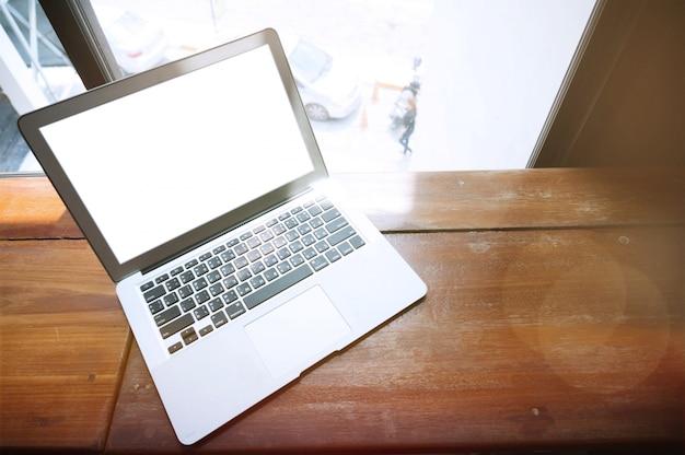 Ноутбук с пустой экран на деревянный стол перед окном офиса.