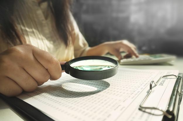 監査人または内部収入サービススタッフ、企業の年次財務諸表を確認するために拡大鏡を使用するビジネス女性。監査コンセプト