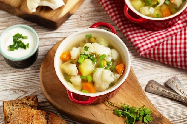 Суп из цветной капусты в миске, хлеб, сливки и сырая цветная капуста