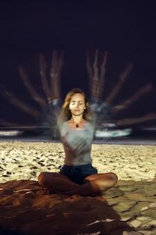 若い女性は瞑想します。長期露出