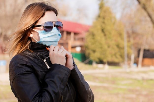 防護マスクとサングラスの若い女性