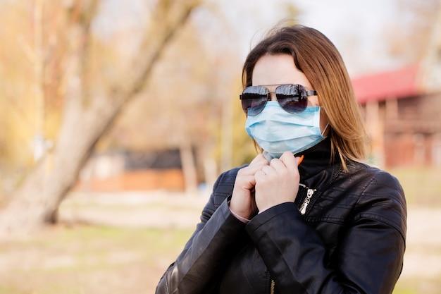 防護マスクとサングラスの女性