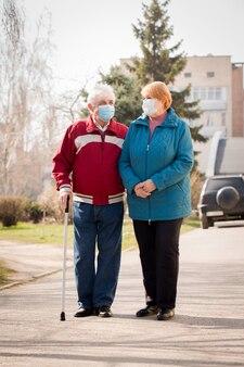 検疫中に通りを歩く老夫婦