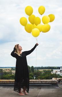 風船の大きな束を持つ女性