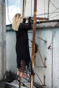 黒のドレスを着た女性が階段を登った