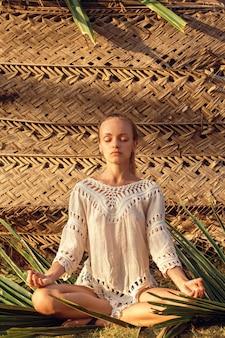 ヤシの葉で瞑想の女性
