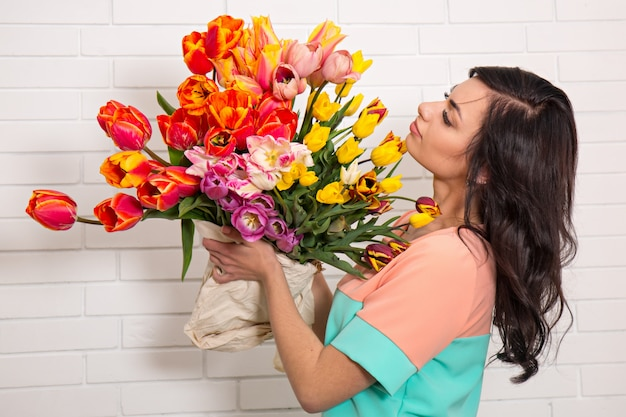 チューリップの大きな花束を持つ女性