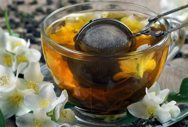 Зеленый чай с жасмином. сухие листья зеленого чая с цветами жасмина и чашка чая на деревянном столе.