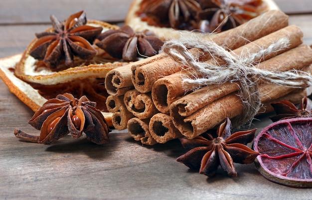 Традиционные специи для глинтвейна. палочки корицы, аниса и сухие цитрусы на деревянном столе.