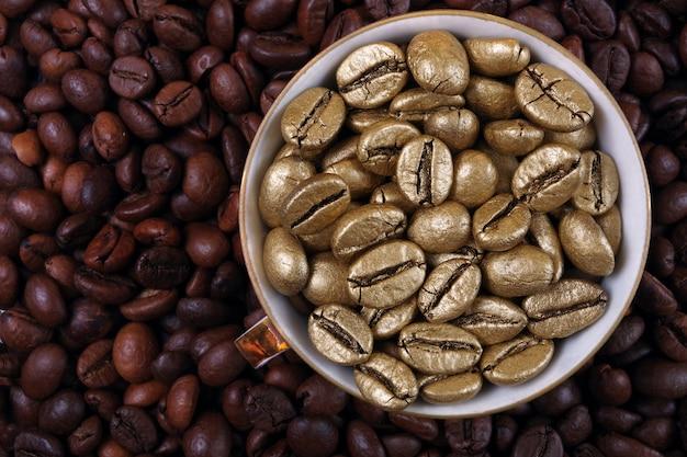 Кофе в зернах текстуры фона. золотые кофейные зерна в чашке. золотой кофе как символ качества и роскоши. понятие роскоши и оригинальности. вид сверху