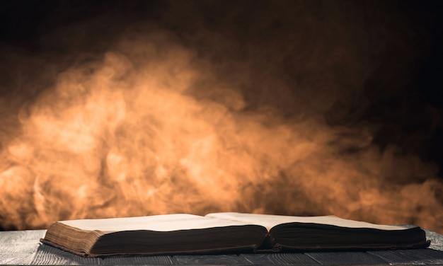 Открытая книга на столе в подсветке с дымом на заднем плане