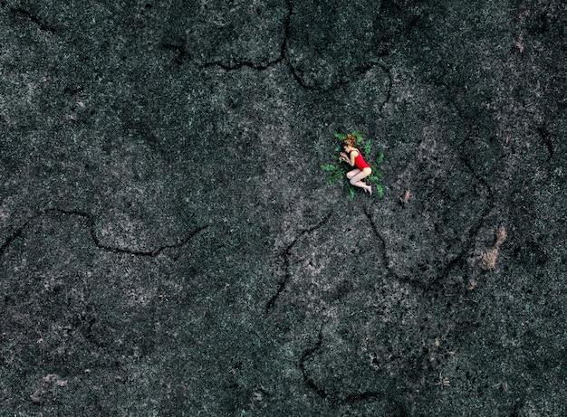 女性は焦げた大地-空からの眺めに横たわっています。