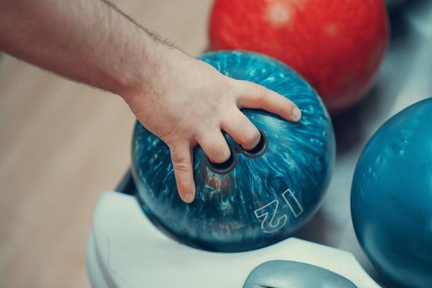 ボウリングのボールを持つ男性の手
